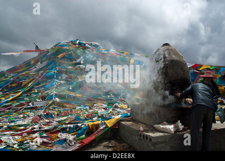 Tibetan couple burning Juniper in Chörten with prayer flags on Khamba La Pass (4794 m), Southern Friendship Highway, - Stock Photo