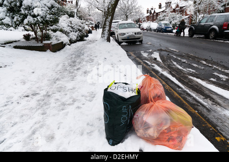 Rubbish awaiting collection at the side of a suburban road in the snow. - Stock Photo