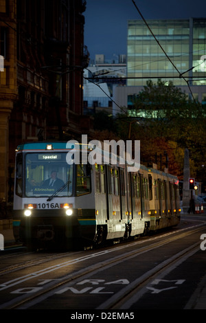 A metrolink tram passing the Midland Hotel (left) as it leaves St Peters Street stop with evening commuters - Stock Photo