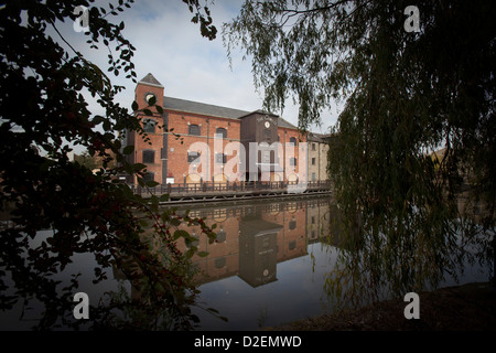 The Orwell Mill reflects in the canal shot through foliage - Stock Photo