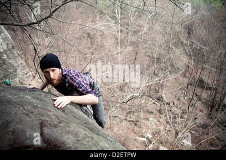 A male rock climber tops on while climbing on a cold day in the northeast. - Stock Photo