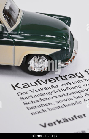 Detail photo of a car sales agreement in German, alongside is a model car - Stock Photo