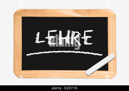 Detail photo of a Chalkboard with the German inscription apprenticeship, white chalk lies in a corner - Stock Photo