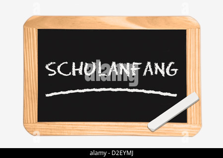 Detail photo of a Chalkboard with the German inscription first day of school, white chalk lies in a corner - Stock Photo