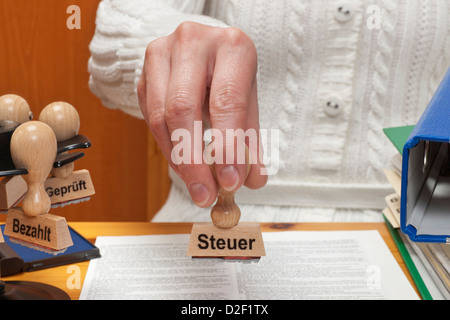 a stamp with the German inscription tax is held in the hand - Stock Photo
