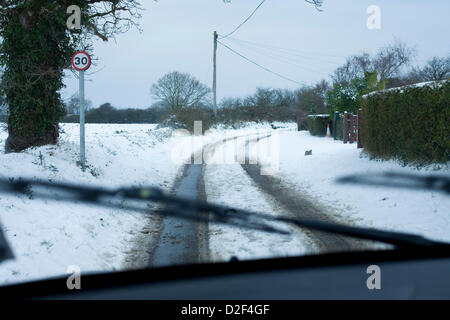 The view from inside a car of snow covered rural roads in Norfolk,UK. A 30 mph speed limit sign can also be seen - Stock Photo