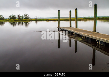 Wooden pier on a misty day reflecting in the water - Stock Photo