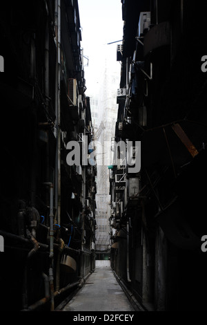 Hong Kong, China, and narrow dark alley with exhaust pipes and air conditioners - Stock Photo
