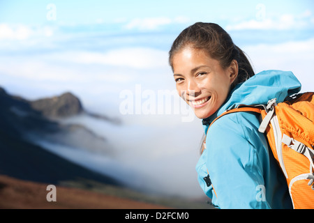 Portrait of happy beautiful young mixed race female hiker hiking in high mountains - Stock Photo