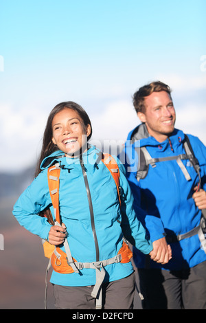 Sporty young happy interracial couple hiking holding hands on mountain hike walking outside high in mountains - Stock Photo