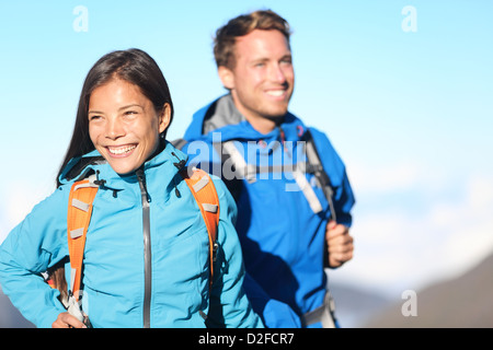 Young interracial couple mixed race couple walking in high mountains with backpack - Stock Photo