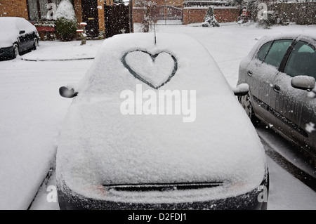 Car with heart drawn in snow on windscreen, Stanwell Moor, Surrey, England, United Kingdom - Stock Photo