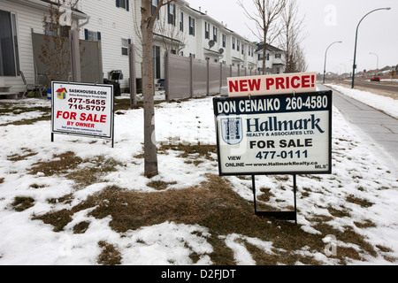 for sale signs outside starter homes in winter Saskatoon Saskatchewan Canada - Stock Photo