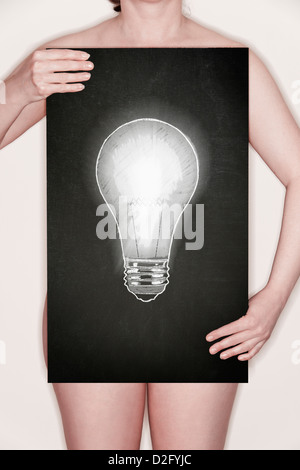 Woman holding a blackboard with an illustration of a light bulb drawn in chalk. - Stock Photo