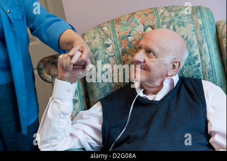 Elderly man in a care home with a carer or nurse / health visitor offering a comforting hand of support - Stock Photo
