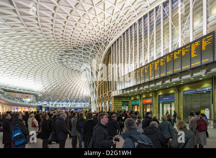 Commuters on Kings Cross station concourse, London, England, UK in the evening rush hour with train delays - Stock Photo