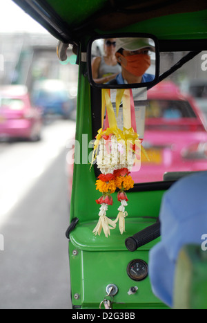 flower garlands hanging from the rear view mirror of a tuk tuk reflecting the driver and passenger in bangkok thailand - Stock Photo