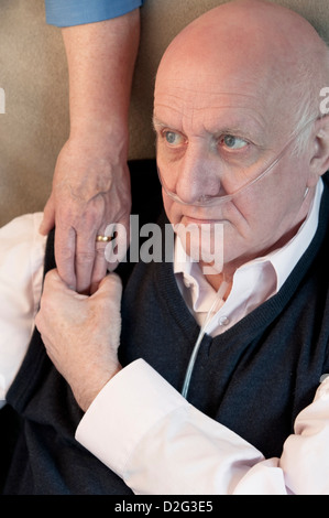 Elderly man in a care home with wife / carer offering a comforting hand of support - Stock Photo