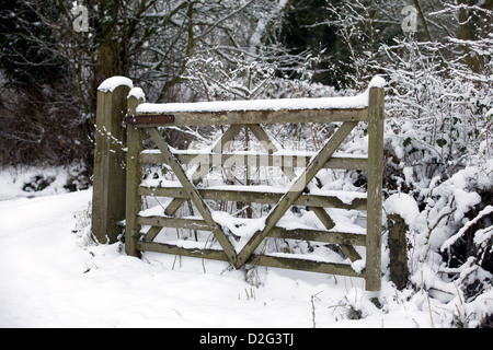 Wooden Five bar gate in the snow on a winters morning British countryside England - Stock Photo
