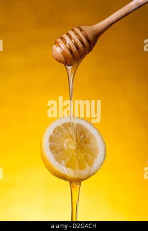 Close-up shot of honey flowing on lemon over yellow background  - Stock Photo