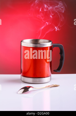 Red travel mug with hot tea spoon - Stock Photo