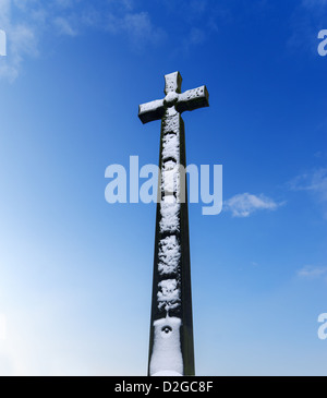 A snow covered DLI South African War Memorial, a Celtic cross against a blue sky Durham City north east England - Stock Photo