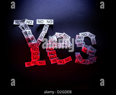 Word yes written of multiple noes on black background illuminated with white and red light. - Stock Photo