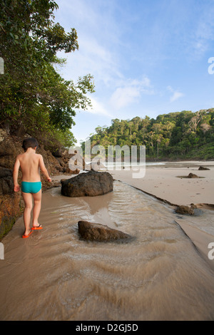 A young Brazilian boy playing on Praia da Ribeira beach, Bahia, Brazil - Stock Photo