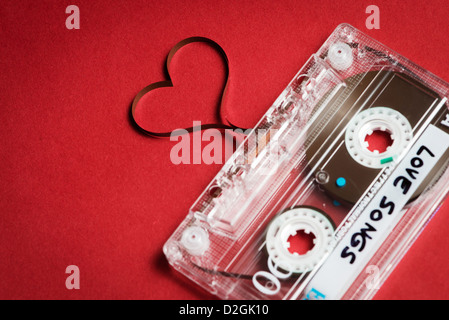 Valentine's day card template - audio cassette with magnetic tape in shape of heart on red background - Stock Photo