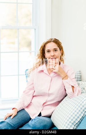 Smiling caucasian woman relaxing on couch by window - Stock Photo