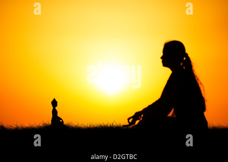 Sunset silhouette of an Indian girl meditating in front of Buddha statue. Andhra Pradesh, India - Stock Photo
