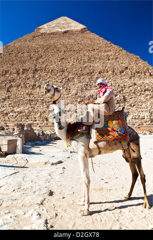 Camel driver poses in front of Pyramid of Khafre/Chefren/Chephren, second-largest Egyptian Pyramid at Giza near - Stock Photo