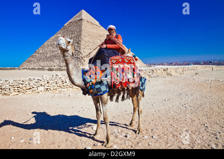 Camel driver poses in front of Pyramid of Khafre or Chefren, second-largest ancient Egyptian Pyramid of Giza near - Stock Photo