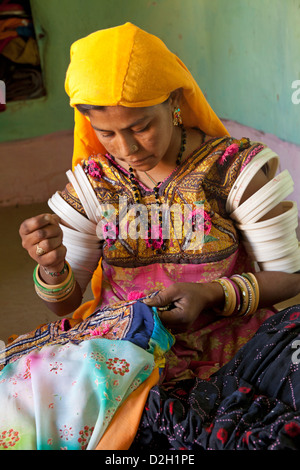 India, Rajasthan, Thar Desert, woman in traditional Rajasthani costume sewing - Stock Photo
