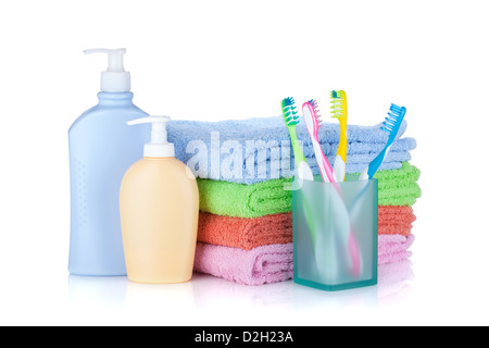 Four colorful toothbrushes, cosmetics bottles and towels. Isolated on white background - Stock Photo