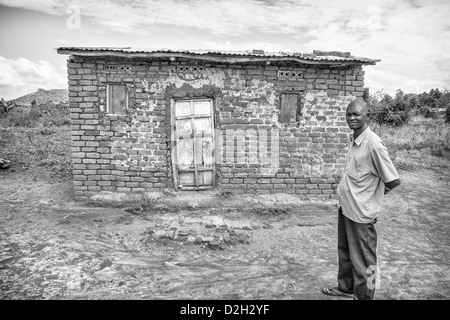 A man stands in front of a rickety house that the village has built - Stock Photo