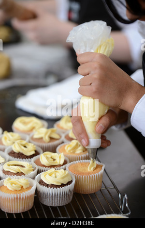 A schoolgirl using an icing bag to top cupcakes during a food Science lesson at Pates Grammar School in Cheltenham, - Stock Photo