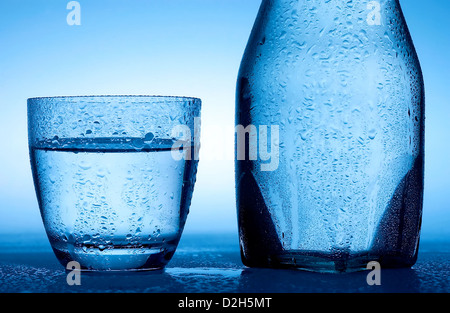 Glass and bottle with water. - Stock Photo