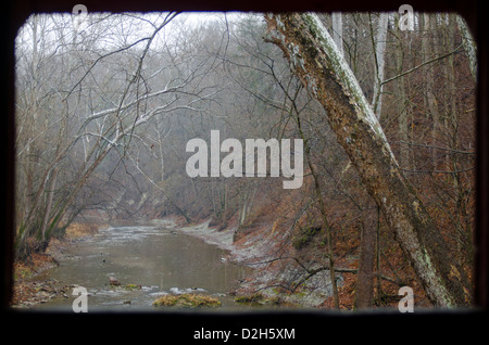 Looking out the window of the Rolling Stone Covered Bridge, just outside of Bainbridge, Indiana, at a winter scene. - Stock Photo