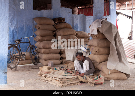 India, Rajasthan, Jodhpur man repairing hessian sacking used for carrying grain - Stock Photo