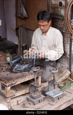 India, Rajasthan, Jodhpur man repairing car tyre inner tube - Stock Photo