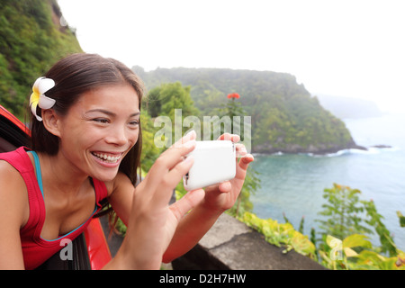 Tourist on Hawaii taking photo with camera phone during car road trip on the famous Road to Hana - Stock Photo