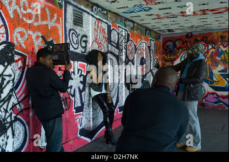 London, Southbank, Riverside, Embankment young black girl female pop singer shooting video in front of  graffiti, - Stock Photo