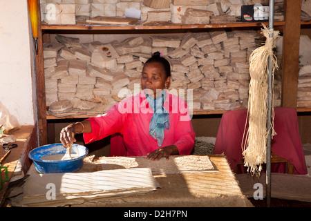 Madagascar, Ambalavao, woman pasting covers of Antaimoro Avoha hand made paper book - Stock Photo