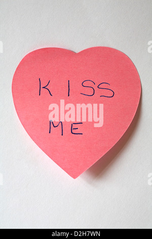 kiss me message written on pink heart shaped post it note pad isolated on white background - Stock Photo