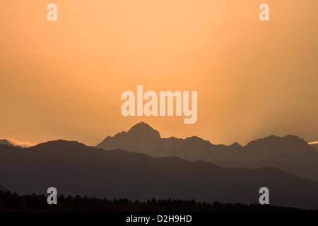 Sun setting behind Mount Triglav, the highest mountain in the Julian Alps, Slovenia. - Stock Photo