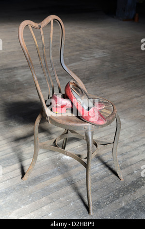 Old red worn out shoes on rusty metal chair with dirty wooden floor for a background. - Stock Photo