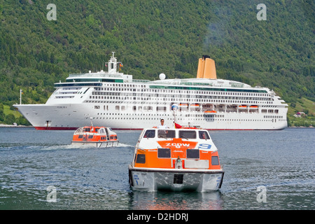 The P&O cruise ship Aurora anchored off Andalsnes, Norway, as her tenders ferry passengers to and from the shore. - Stock Photo