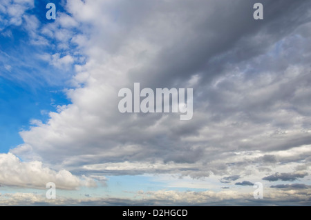 Blue sky with cumulus clouds in background and a large cloud front. - Stock Photo
