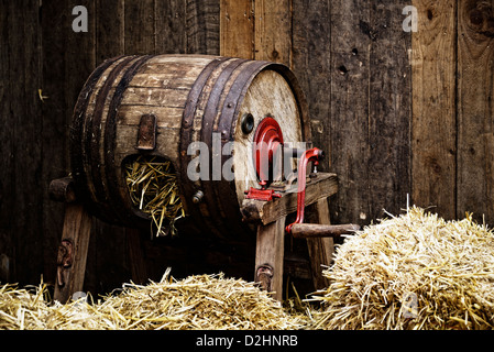 Vintage barrel-type butter churn filled with straw, wooden background - Stock Photo